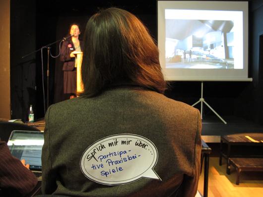 """Teilnehmer der Tagung erhielten Aufkleber mit der Aufschrift: """"Sprich mit mir über..."""". Die Antwort dieser Teilnehmerin lautete: """"...Partizipation und Praxisbeispiele"""""""